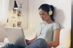 Przypadkowy młodej kobiety obsiadanie na łóżku i używać w domu laptopie Zdjęcia Royalty Free