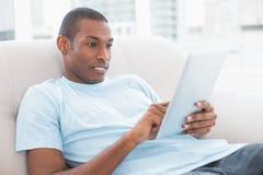 Przypadkowy młody Afro mężczyzna używa cyfrową pastylkę na kanapie Zdjęcie Royalty Free
