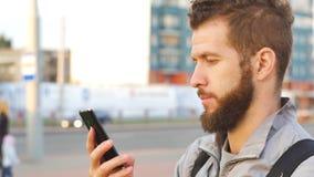Przypadkowy młody biznes opowiada na mądrze telefonu Przystojnym młodym biznesowym mężczyzna opowiada na smartphone zdjęcie wideo