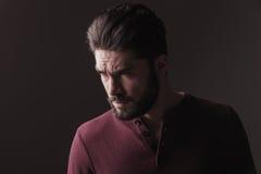 Przypadkowy młody człowiek patrzeje gniewny zdala od kamery Obraz Royalty Free