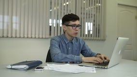 Przypadkowy młody człowiek pracuje w biurze na klawiaturze, siedzący przy biurkiem, pisać na maszynie zbiory