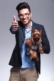 Przypadkowy młody człowiek trzyma szczeniaka i pokazuje kciuk up fotografia stock