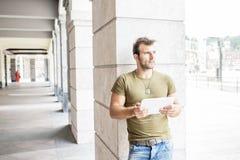 Przypadkowy nowożytny mężczyzna z pastylka komputerem w uliczny patrzeć daleko od zdjęcia stock