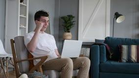 Przypadkowy obsiadanie Excited mężczyzna odświętności sukces na laptopie zbiory