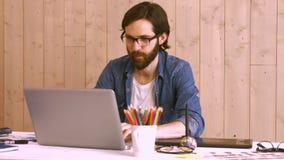Przypadkowy pracownik przy jego biurkiem używać laptop zbiory