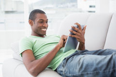 Przypadkowy uśmiechnięty Afro mężczyzna używa cyfrową pastylkę na kanapie Zdjęcie Stock
