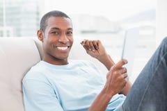 Przypadkowy uśmiechnięty Afro mężczyzna używa cyfrową pastylkę na kanapie Obrazy Royalty Free
