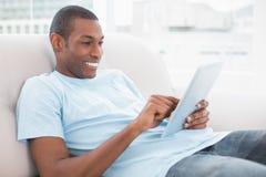 Przypadkowy uśmiechnięty młody Afro mężczyzna używa cyfrową pastylkę na kanapie Zdjęcia Stock