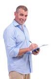 Przypadkowy w średnim wieku mężczyzna pisze na schowku Fotografia Royalty Free