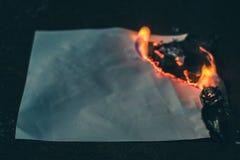 Przypalał papierowego prześcieradło na zmroku Obrazy Stock