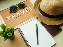 Przypomnienie deska z abecadłami PODRÓŻUJE, pusty ślimakowaty notatnik, pióro, paszport, kapelusz i okulary przeciwsłoneczni, Zdjęcia Royalty Free