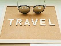 Przypomnienie deska z sformułowaniami PODRÓŻUJE i okulary przeciwsłoneczni z słowa odbiciem Obrazy Stock