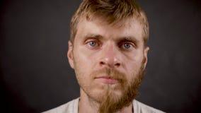 Przyrodni brodaty mężczyzna wiruje twarz w ciemnym odosobnionym studiu zbiory wideo