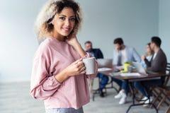 Przyrodni długość portret Afrykańska żeńska cieszy się kawa w biurze, rozochocona młoda biznesowa kobieta satysfakcjonował z pomy zdjęcie stock
