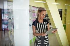 Przyrodni długość portret młody piękny kobieta konsultant trzyma cyfrową pastylkę podczas gdy stojący w kosmetyka sklepie fotografia royalty free