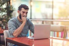Przyrodni długość portret pomyślny brodaty projektant ono uśmiecha się przy kamerą podczas gdy pracujący na freelance przy netboo zdjęcia stock