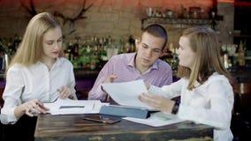 Przyrodnia długość młody biznesowy mężczyzna i kobiety siedzi w barze dyskutuje coś zbiory