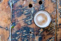 Przyrodnia pełna piwna filiżanka na górze drewnianego stołu Zdjęcie Stock
