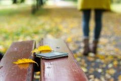 Przyschnięty smartphone na parkowej ławce obrazy royalty free