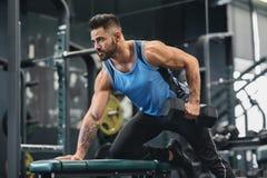 Przystojna atleta opracowywa z dumbbell przy gym fotografia royalty free