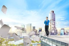 Przystojna azjatykcia biznesmen pozycja z latanie papierem na budynku dachu fotografia stock