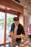Przystojna azjatykcia m??czyzna kupienia piekarnia dla kawowej przerwy w popo?udniu Piekarnia i Kawowa przerwa obraz stock