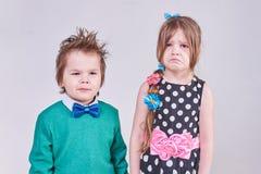 Przystojna chłopiec, będący ubranym błękitnego łęku krawat i zielonego pulower, śmia się przy płacz dziewczyną Obrazy Royalty Free