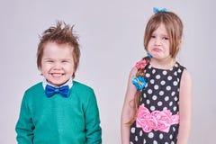 Przystojna chłopiec, będący ubranym błękitnego łęku krawat i zielonego pulower, śmia się przy płacz dziewczyną Zdjęcie Royalty Free
