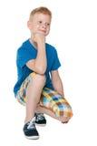 Przystojna chłopiec w błękitnej koszula siedzi fotografia royalty free
