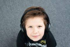 Przystojna chłopiec w hełmofonach obrazy stock