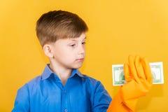 Przystojna chłopiec w płuczkowych rękawiczkach trzyma zwitek dolary w jeden ręce i spojrzenia przy nim Pojęcie pranie brudnych pi fotografia royalty free