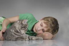 Przystojna chłopiec z ślicznym kotem zdjęcia stock