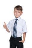 Przystojna chłopiec trzyma jego kciuk up Zdjęcia Stock