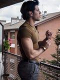 Przystojna ciemna z włosami młody człowiek pozycja w balkonie Obrazy Stock