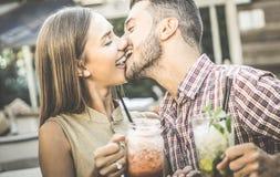 Przystojna mężczyzna całowania młoda kobieta przy moda koktajlu barem Zdjęcie Stock