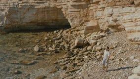 Przystojna mężczyzna fala ręka na skalistym seashore zbiory