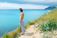 Przystojna mężczyzna pozycja na wzgórzu i patrzeć na morzu Boczny widok Zdjęcie Stock