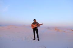 Przystojna męska Arabska bawić się gitary pozycja w środku bottomle Obraz Stock