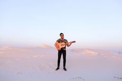 Przystojna męska Arabska bawić się gitary pozycja w środku bottomle Zdjęcia Royalty Free