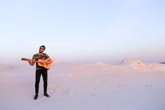 Przystojna męska Arabska bawić się gitary pozycja w środku bottomle Obrazy Royalty Free