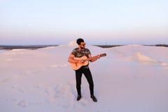 Przystojna męska Arabska bawić się gitary pozycja w środku bottomle Zdjęcie Royalty Free
