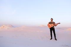 Przystojna męska Arabska bawić się gitary pozycja w środku bottomle Zdjęcia Stock
