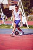 Przystojna męska bawić się koszykówka plenerowa fotografia stock