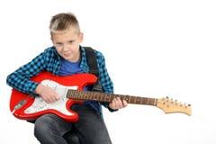 Przystojna młoda chłopiec bawić się na czerwonej gitarze elektrycznej Zdjęcia Stock