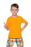 Przystojna młoda chłopiec z jego kciukiem up obrazy royalty free