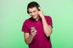 Przystojna młody człowiek pozycja i słuchająca muzyka Obrazy Stock