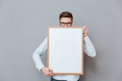 Przystojna młoda brodata biznesmena mienia copyspace deska Fotografia Stock
