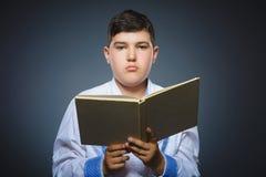Przystojna mała zaakcentowana chłopiec z książką odizolowywającą na szarym tle obrazy stock