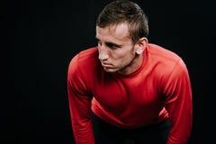Przystojna mięśniowa atleta bierze przerwy pozycję przeciw ciemnemu tłu Zmęczony młody Kaukaski biegacz odpoczywa po ciężkiego sz Zdjęcie Stock