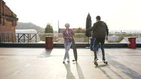 Przystojna potomstwo para ma zabawę z jeździć na deskorolce na dachu nowożytny budynek przy zmierzchem Dwa przyjaciół przejażdżka zdjęcie wideo